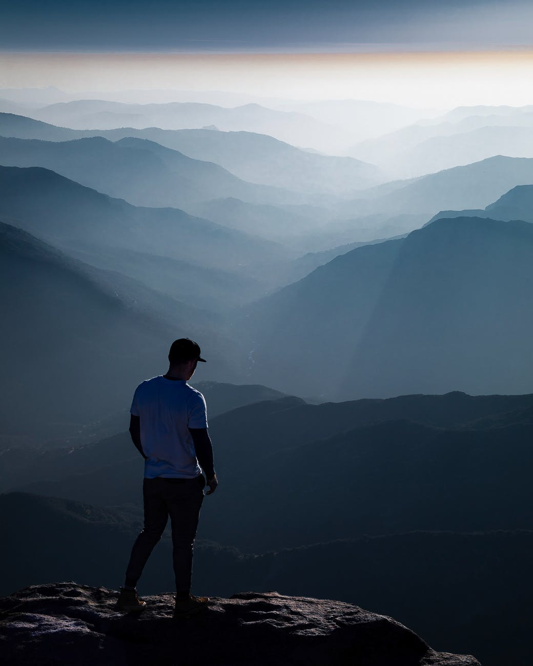 male traveler standing on top of mountain and admiring landscape